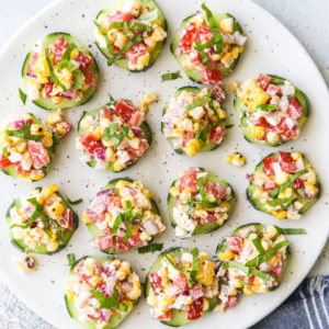 Individual cucumber bites topped with a corn and red pepper salad filled with feta, basil, and a creamy dressing.