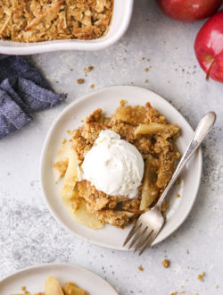 close up of classic apple crisp on plates with ice cream