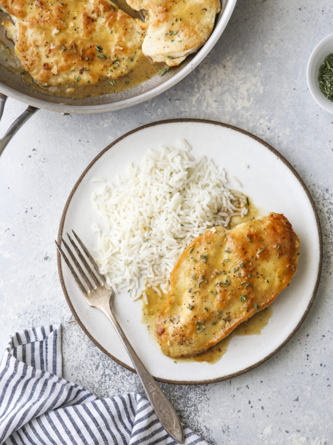 easy skillet chicken with herb butter sauce on a plate with rice