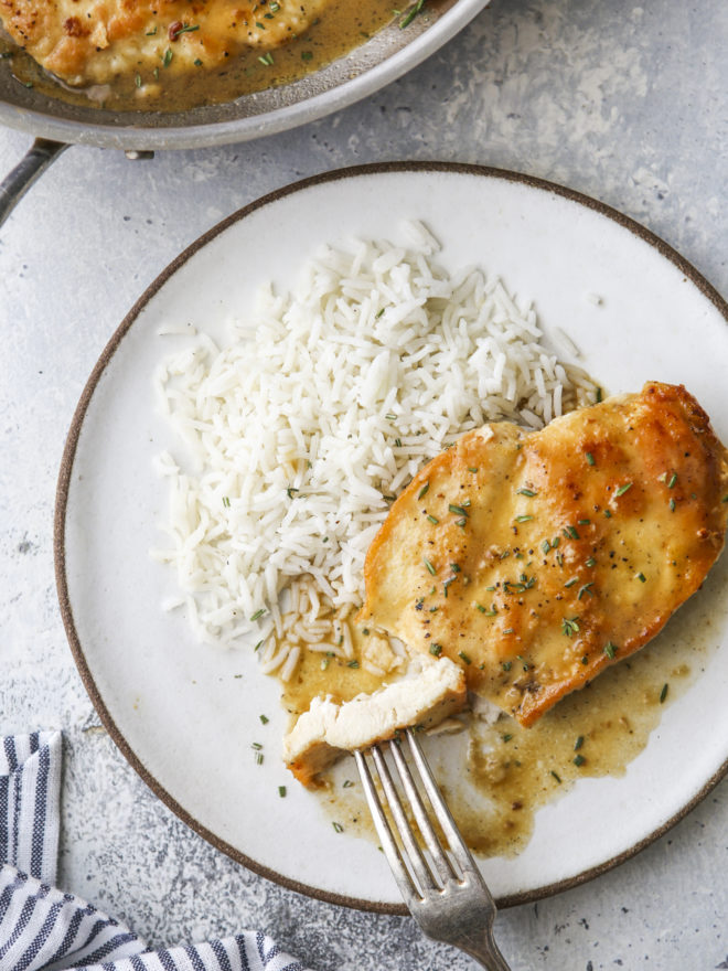 taking a bite of skillet chicken with sauce and rice