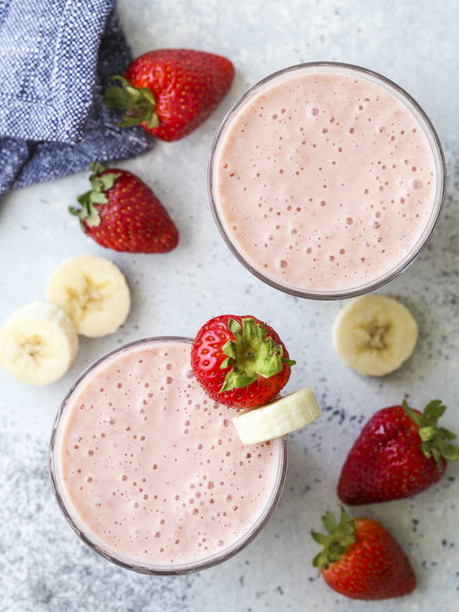 strawberry banana smoothie in cup with fruit from overhead