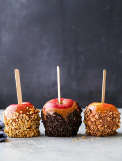 Three caramel apples with different toppings