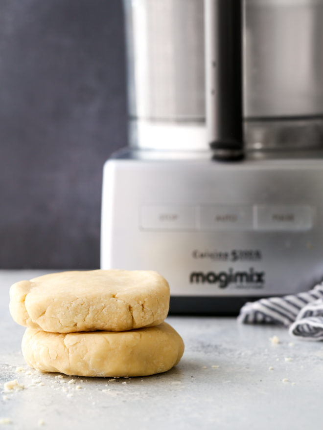 pie crust disks stacked in front of a food processor