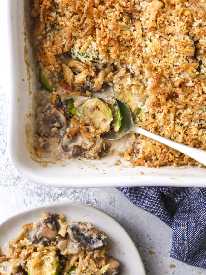 scooping brussels sprout and mushroom casserole out of baking dish