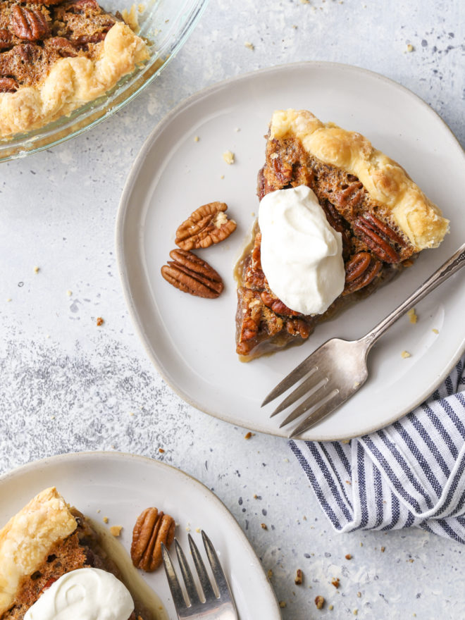pecan pie slices on plates with whipped cream