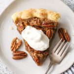 pecan pie piece with whipped cream on top