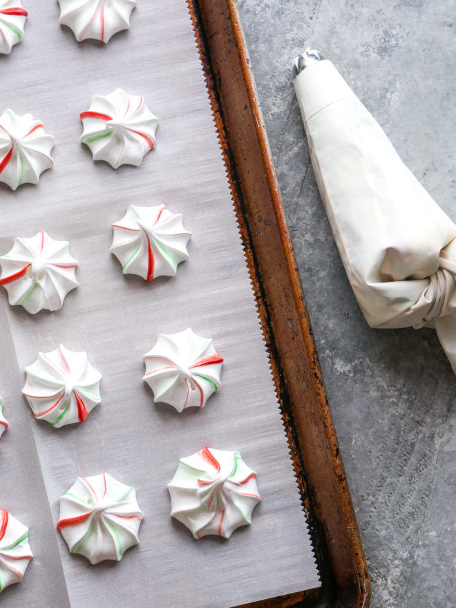 piped meringues on a sheet pan with piping bag