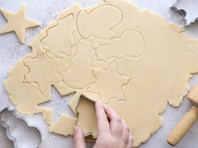 cutting out rolled cookie dough with christmas cookie cutters