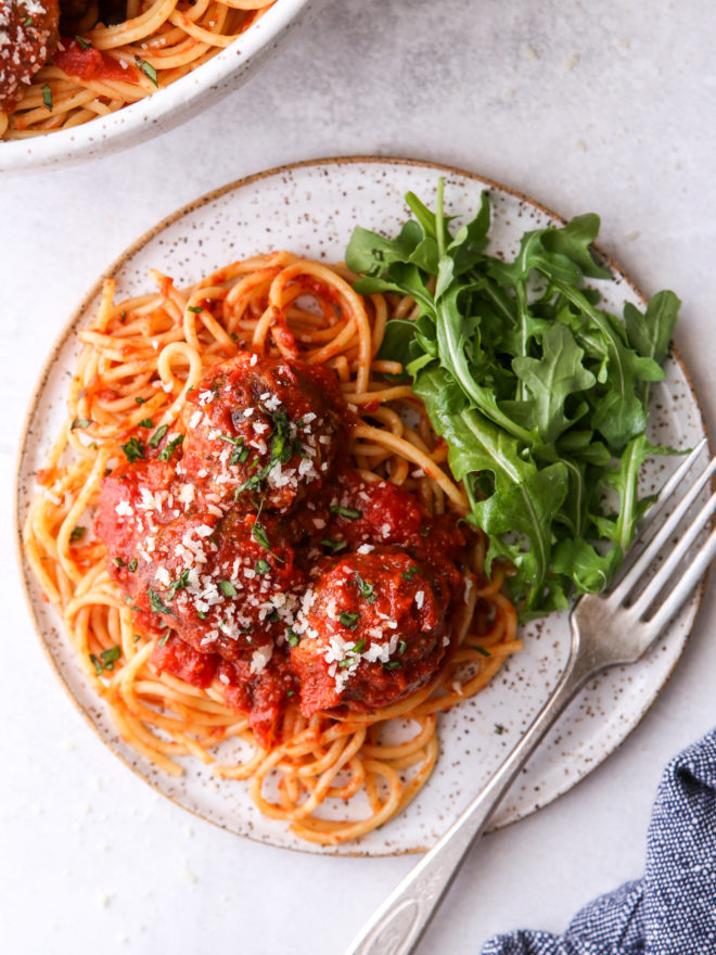 spaghetti and meatballs on a plate with salad