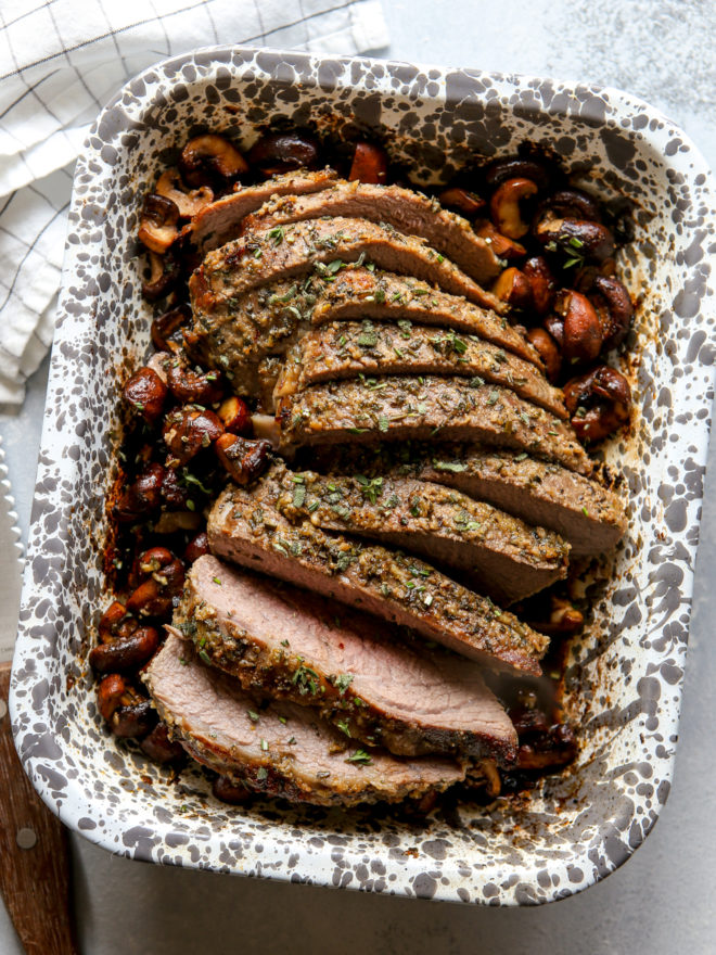 garlic and herb tri-tip roast with mushrooms sliced in baking dish