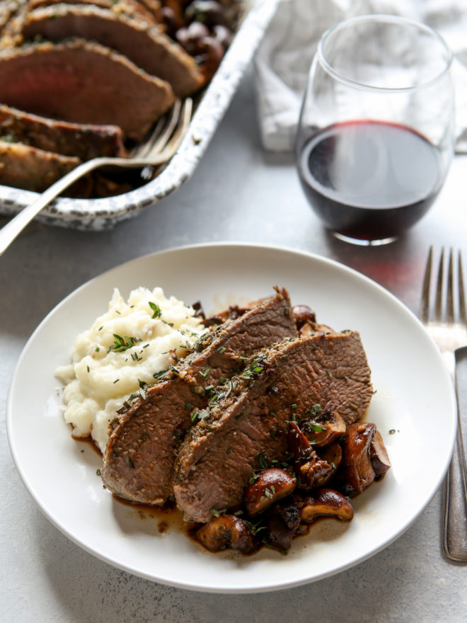 garlic and herb tri-tip roast with mushrooms on a plate
