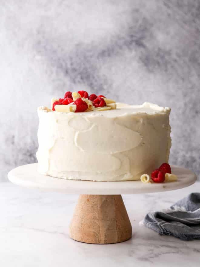 raspberry white chocolate cake on a cake stand