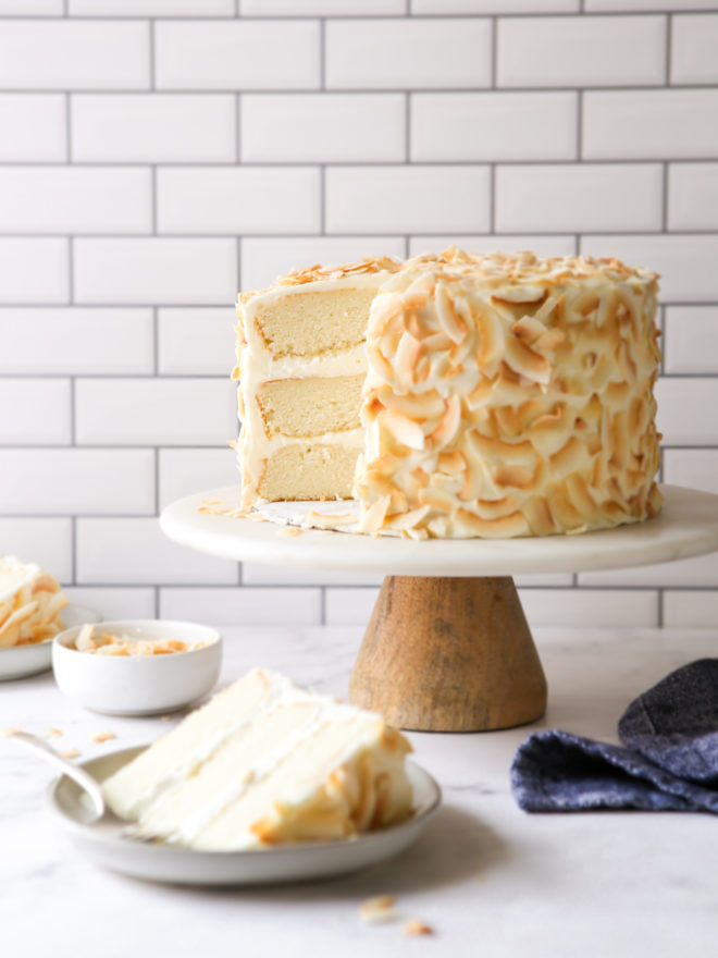 southern coconut cake on a cake stand with a slice on a plate