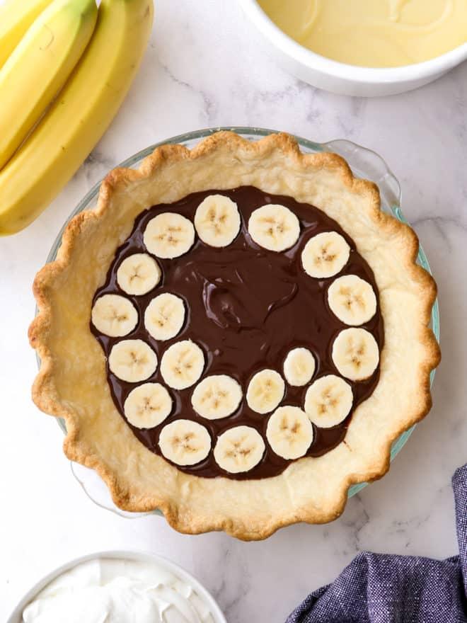 assembling chocolate bottom banana cream pie