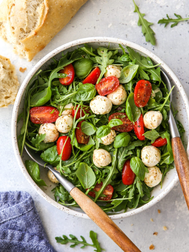 arugula caprese salad in a bowl with bread on the side