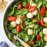 closeup of arugula caprese salad in a bowl