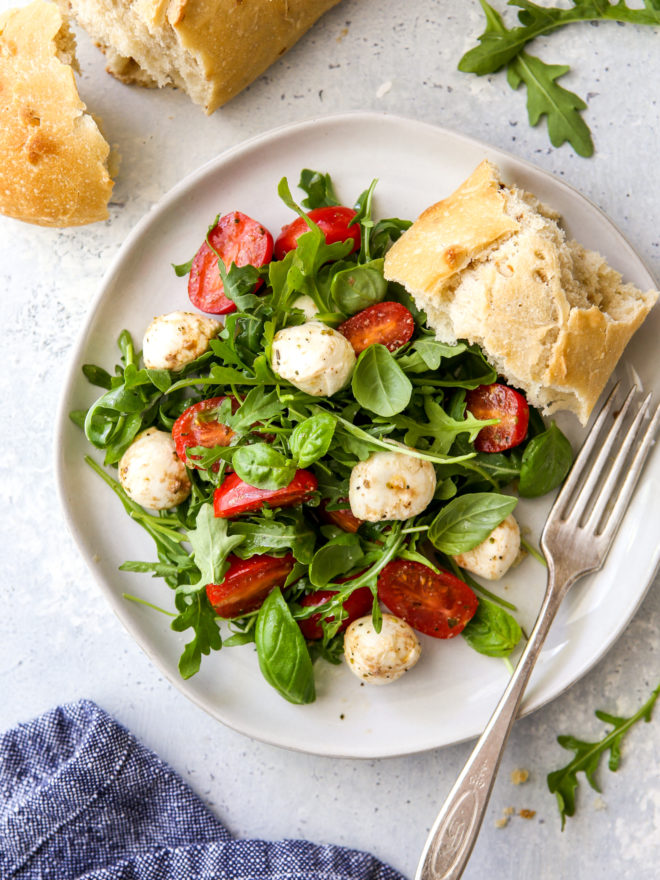 arugula caprese salad on a plate with a slice of bread
