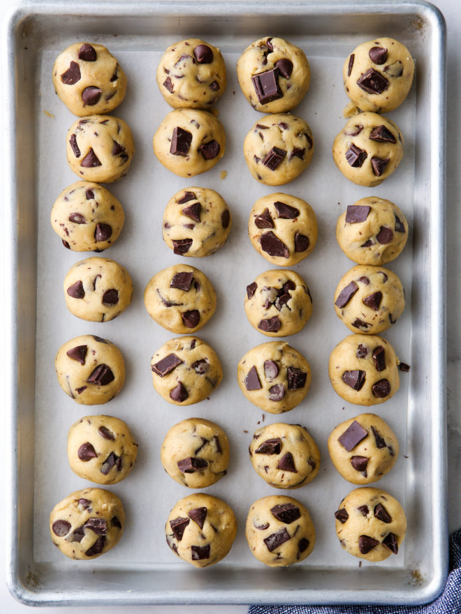rounds of chocolate chip cookie dough on a sheet pan