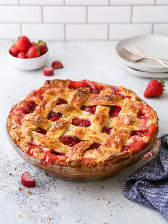 strawberry rhubarb pie on table with stack of plates