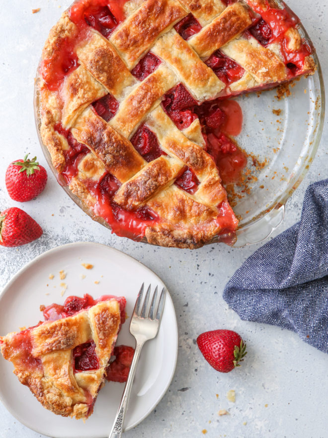 strawberry rhubarb pie with a slice on a plate