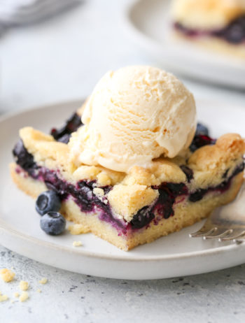 blueberry pie bars with a scoop of ice cream on a plate