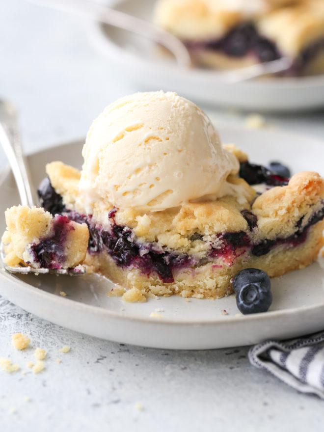 blueberry pie bars with a scoop of ice cream on a plate, bite taken out