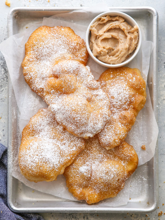 fry bread on a pan with cinnamon honey butter in a bowl