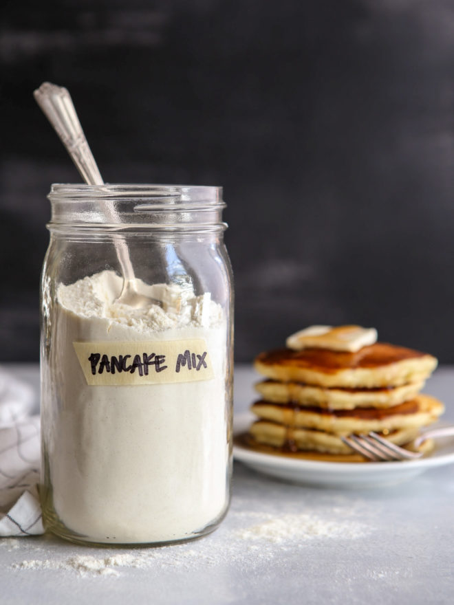 buttermilk pancake mix with stack on pancakes on a plate in the background