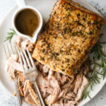 slow cooker rosemary balsamic pork roast shredded on a plate