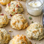 buttermilk drop biscuits with different mixins on a sheet of parchment closeup