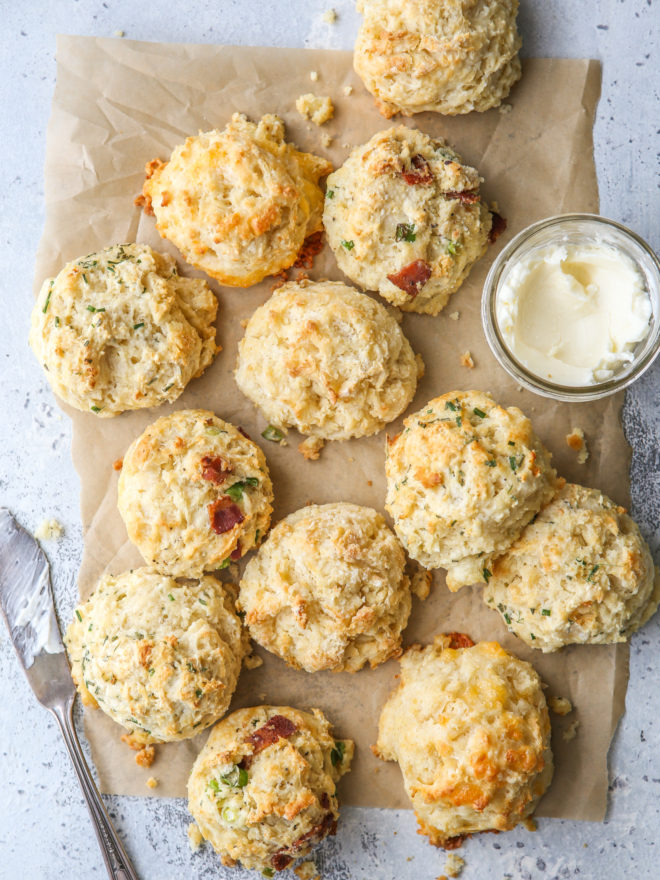 buttermilk drop biscuits with different mixins on a sheet of parchment