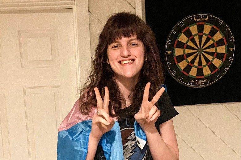 Esmée Silverman, smiling, holds her hands in peace signs and wears a transgender flag draped over her shoulders.