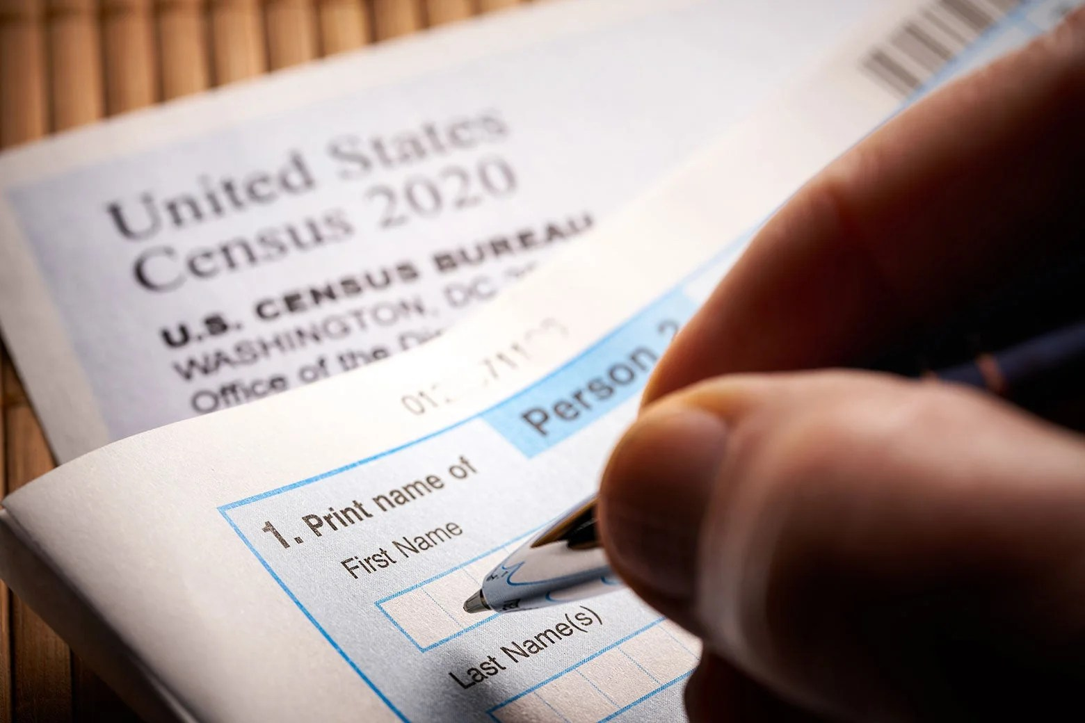 A person's hand filling out the 2020 census form.