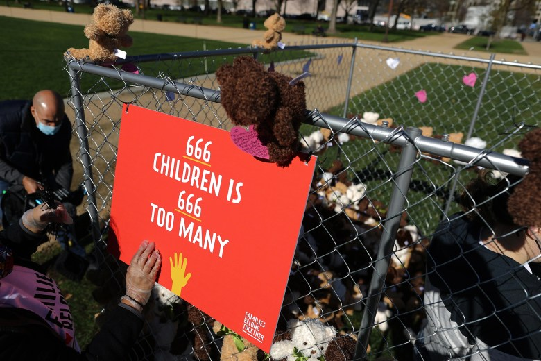 """A cage full of teddy bears with a sign on it that says """"666 children is 666 too many"""""""
