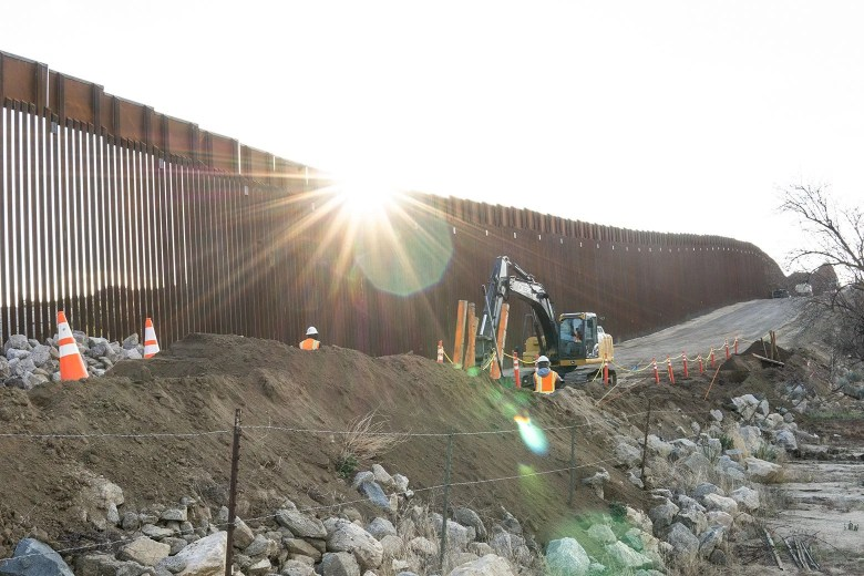 Late sun flares through the top of the United States border wall as a crew works around an excavator, in a strip of dirt, rubble, and barbed wire.