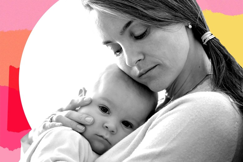 A woman holding her baby closely.