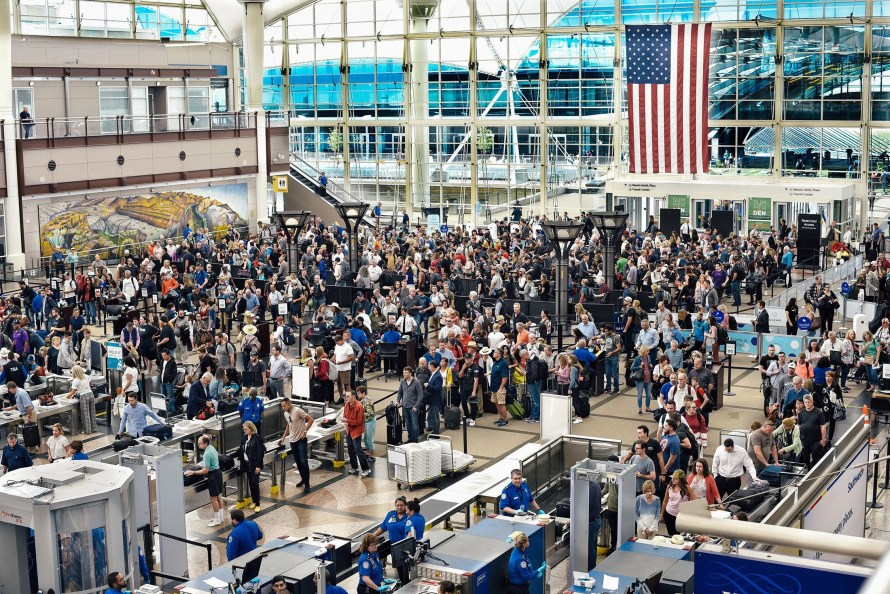 A long line of passengers wait to enter security screening at an airport.