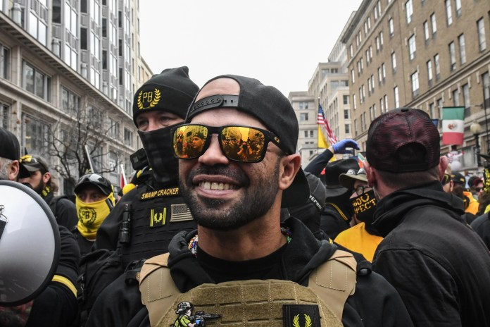 Enrique Tarrio wears sunglasses, a backward cap, and a bulletproof vest, during a downtown rally.