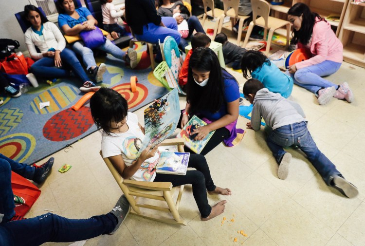 Children read and draw in a playroom as moms look on