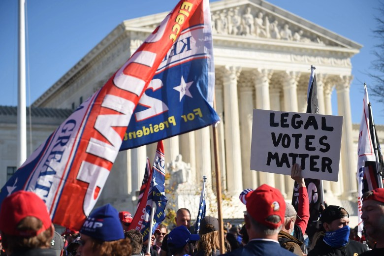 """Trump supporters wave signs that read """"LEGAL VOTES MATTER"""" and """"TRUMP 2020"""" in front of the Supreme Court."""