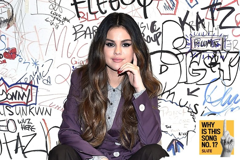 Selena Gomez in front of a wall with hand-written graffiti.
