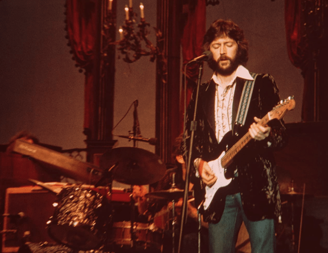 Eric Clapton stands on stage behind a microphone, holding a guitar
