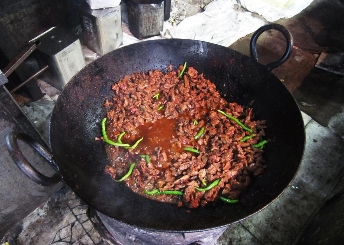 A dish of tallava gosht slow frying in peanut oil on a cast-iron tava at the entrance to Al-Hamdullillah.