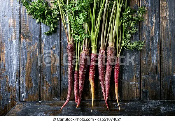 Bundle of purple carrot. Bundle of raw organic purple carrot with green top haulm over old wooden plank background. top view with copy space. food ...