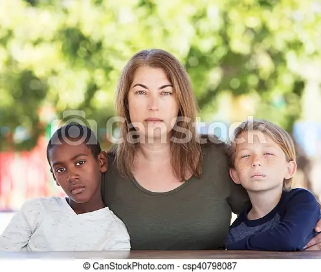Serious Mom Sitting With Sons At Park Table Csp