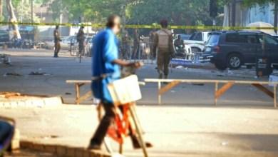 Un cycliste passe près de l'état-major des forces armées, au lendemain des attentats du 3 mars 2018 à Ouagadougou | AFP | Ahmed OUOBA