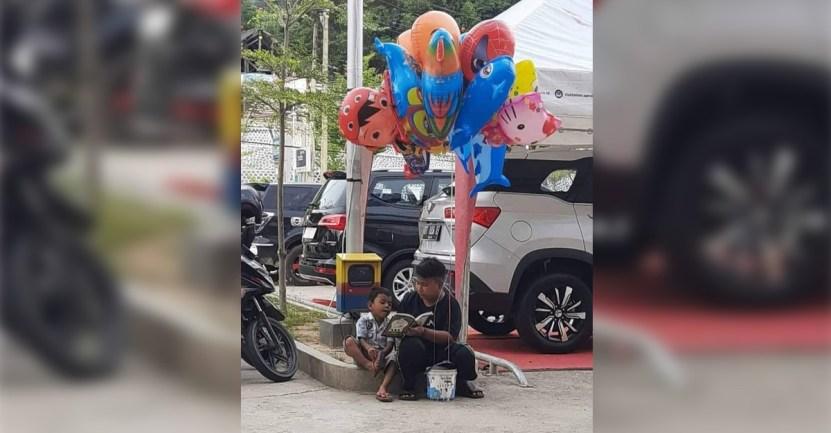 nino vende globos leen - Niño le enseña a leer a su hermano menor mientras vende globos en la calle. Sobreviven de a dos