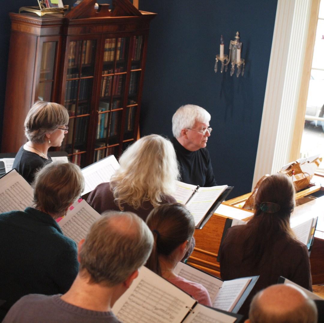 David Smith at piano with chorus rehearsing