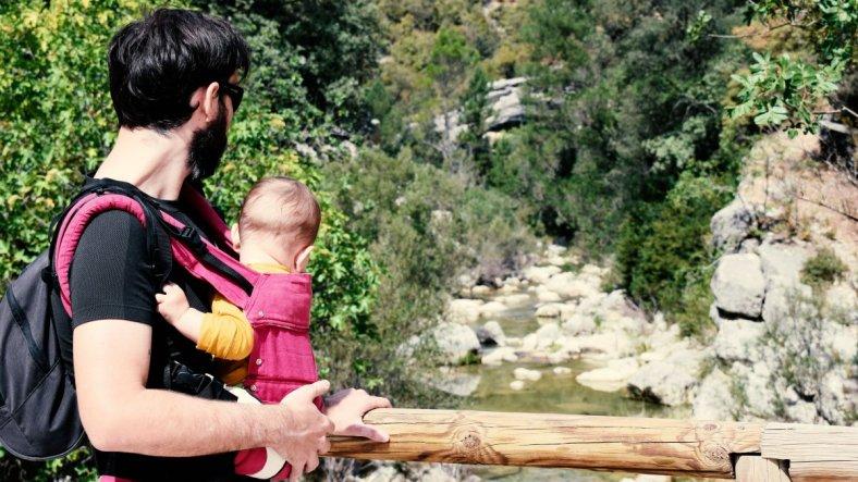 Hija única, porque hemos decidido no tener más hijos, padre porteando a un bebé en paraje natural