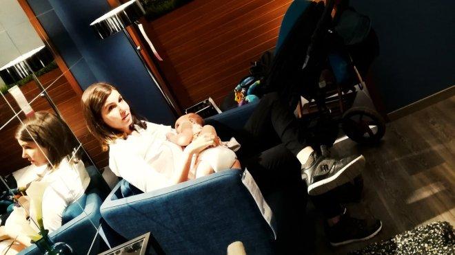 Madre dando el pecho en público, sentada en un sillón de una exposición de Ikea, mientras su pareja le ofrece un poco de intimidad, en su papel de padre avtivo y protector de la lactancia materna.